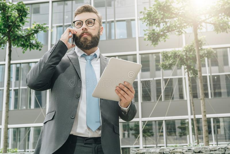 Ο νέος επιχειρηματίας στέκεται υπαίθριος, κρατά τον υπολογιστή ταμπλετών και μιλά στο τηλέφωνο κυττάρων του στοκ εικόνες
