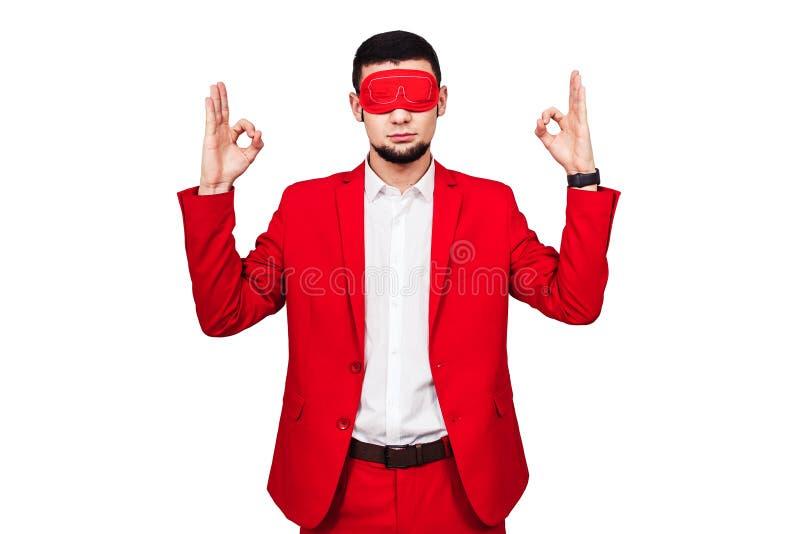 Ο νέος επιχειρηματίας στηρίζεται στην τύχη, τύχη γενειοφόρο άτομο σε ένα κόκκινο κοστούμι με ένα κόκκινο blindfold στοκ εικόνες