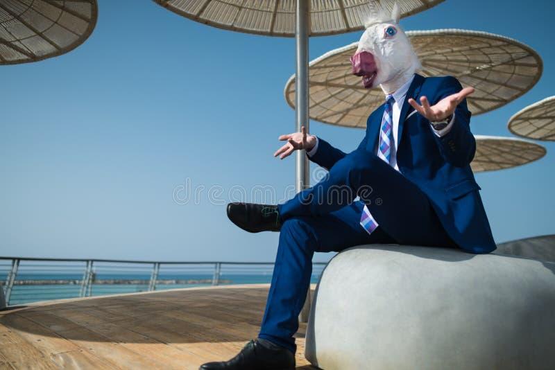 Ο νέος επιχειρηματίας στο κοστούμι κάθεται κάτω από τις ομπρέλες στην προκυμαία πόλεων στοκ εικόνες
