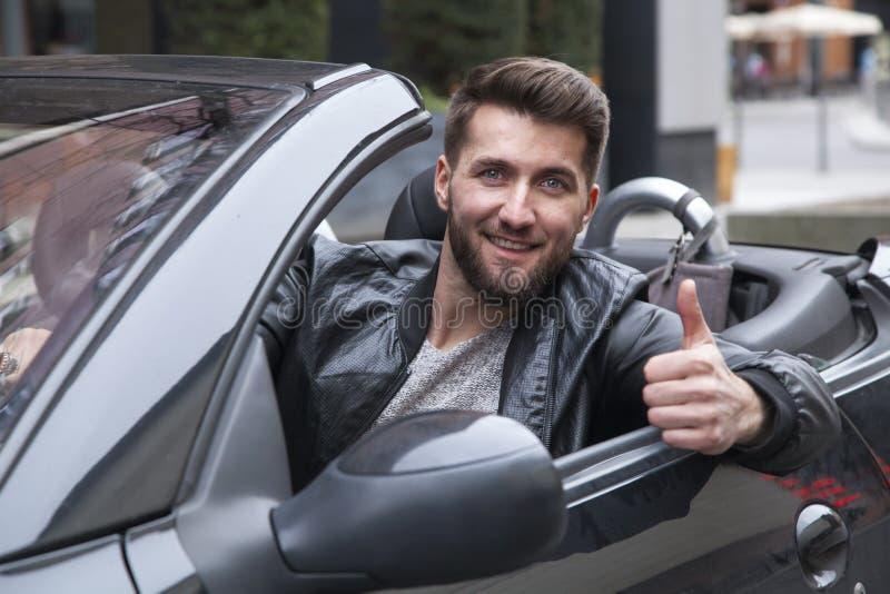 Ο νέος ευτυχής επιχειρηματίας σε ένα καμπριολέ δείχνει τον αντίχειρά του επάνω στοκ φωτογραφία