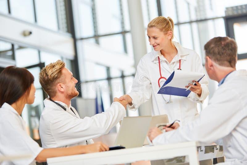 Ο νέος θηλυκός γιατρός καλωσορίζει έναν συνάδελφο με τη χειραψία στοκ εικόνα με δικαίωμα ελεύθερης χρήσης