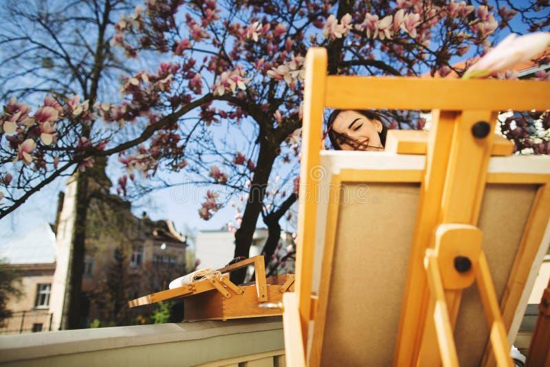Ο νέος καλλιτέχνης γυναικών brunette χρωματίζει μια εικόνα κοντά στο δέντρο magnolia Easel στο πρώτο πλάνο στοκ φωτογραφία