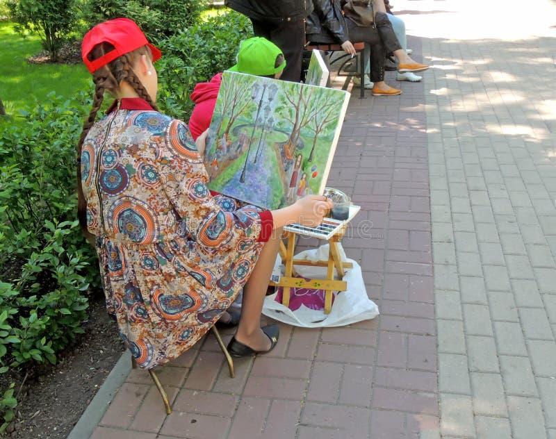 Ο νέος καλλιτέχνης γυναικών εξετάζει τη χρωματισμένη εικόνα στοκ φωτογραφίες