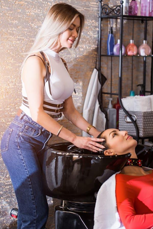 Ο νέος κουρέας γυναικών, κομμωτής πλένει την τρίχα του πελάτη στοκ εικόνες