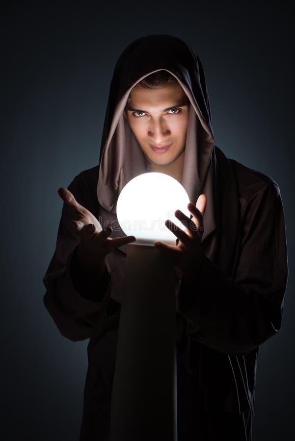 Ο νέος μάγος με τη σφαίρα κρυστάλλου στο σκοτεινό δωμάτιο στοκ εικόνα με δικαίωμα ελεύθερης χρήσης