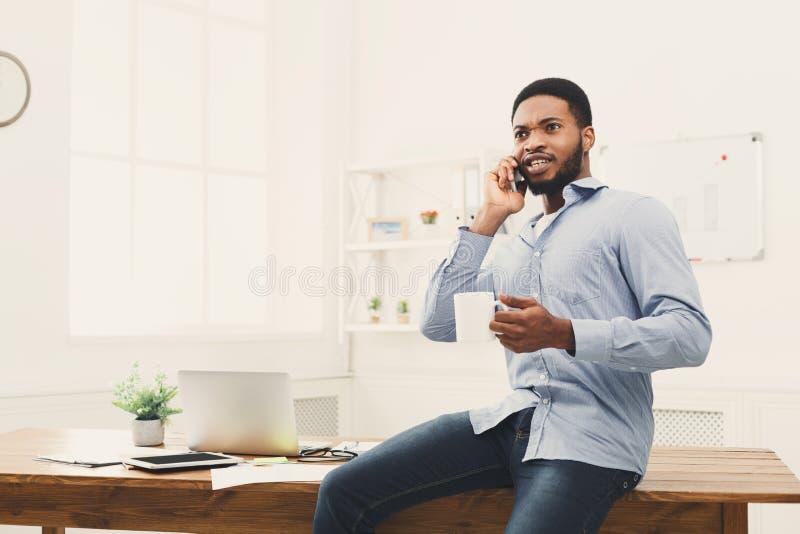 Ο νέος μαύρος επιχειρηματίας διοργανώνει την κινητή τηλεφωνική συζήτηση στοκ εικόνα