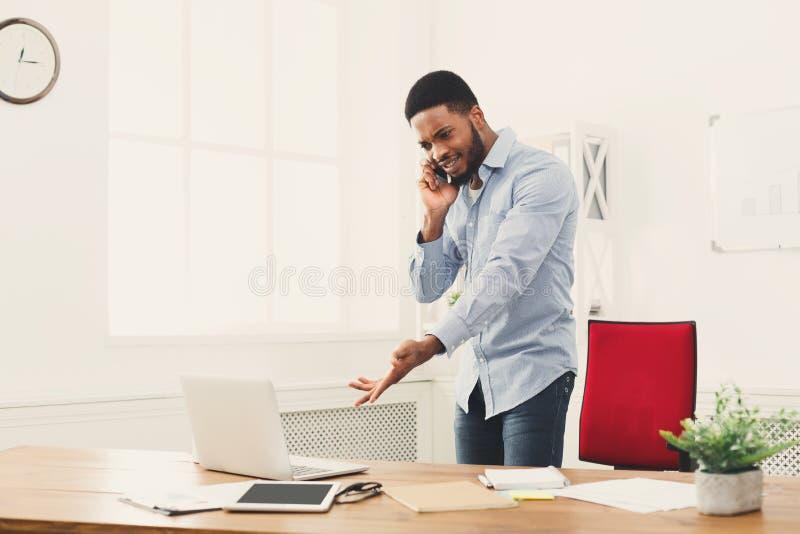 Ο νέος μαύρος επιχειρηματίας διοργανώνει την κινητή τηλεφωνική συζήτηση στοκ φωτογραφία