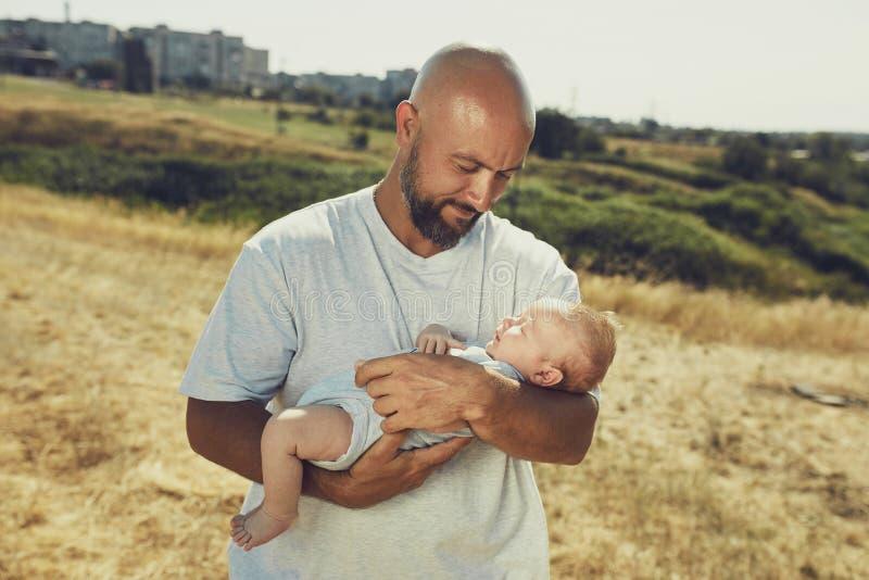 Ο νέος μπαμπάς κρατά ένα νεογέννητο μωρό περπατώντας στη φύση ο ευτυχής πατέρας φορά τα σορτς και μια μπλούζα E στοκ φωτογραφίες