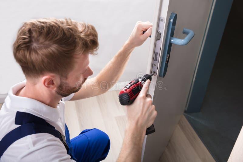 Ο νέος ξυλουργός εγκαθιστά την κλειδαριά πορτών στοκ φωτογραφία με δικαίωμα ελεύθερης χρήσης