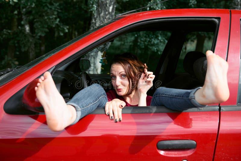 Ο νέος οδηγός γυναικών που στηρίζεται σε ένα κόκκινο αυτοκίνητο, έβαλε τα πόδια της στο παράθυρο και το φλερτ αυτοκινήτων, ευτυχή στοκ εικόνα με δικαίωμα ελεύθερης χρήσης
