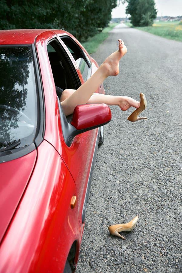 Ο νέος οδηγός γυναικών που στηρίζεται σε ένα κόκκινο αυτοκίνητο, έβαλε τα πόδια της στο παράθυρο αυτοκινήτων, ευτυχής έννοια ταξι στοκ εικόνες