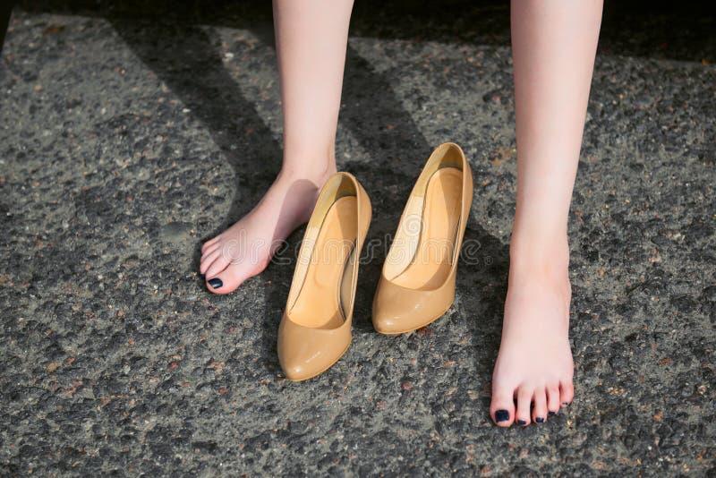 Ο νέος οδηγός γυναικών που στηρίζεται σε ένα κόκκινο αυτοκίνητο, έβγαλε τα παπούτσια τους, ευτυχής έννοια ταξιδιού, τα υψηλά παπο στοκ φωτογραφία