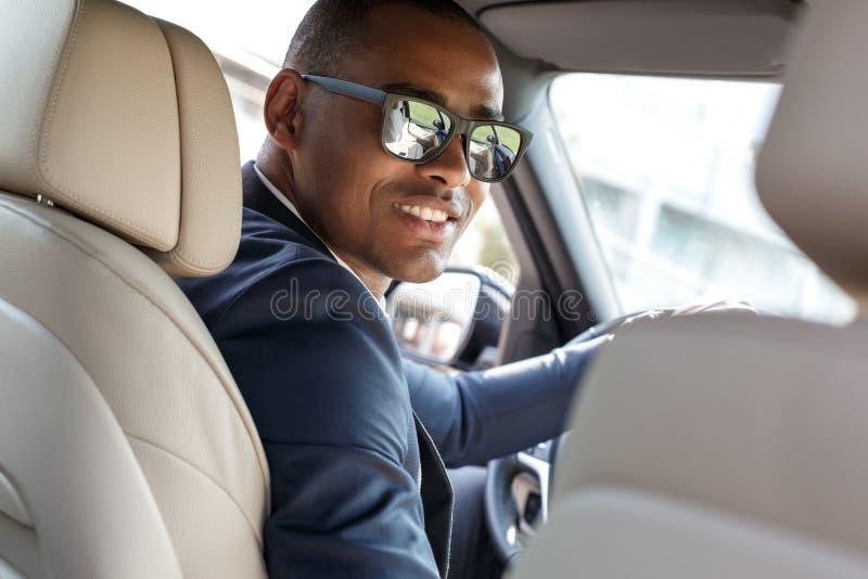 Ο νέος οδηγός επιχειρηματιών στα γυαλιά ηλίου που κάθεται μέσα στην οδήγηση αυτοκινήτων που φαίνεται πίσω κάμερα χαλάρωσε την κιν στοκ εικόνα
