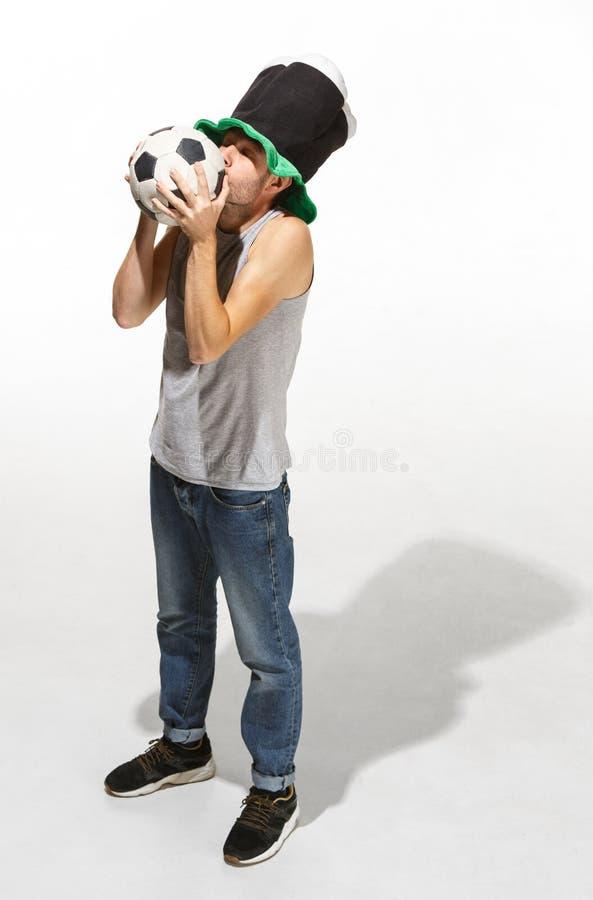 Ο νέος οπαδός ποδοσφαίρου - άτομο που αγκαλιάζει τη σφαίρα ποδοσφαίρου που απομονώνεται σε ένα άσπρο υπόβαθρο στοκ φωτογραφίες