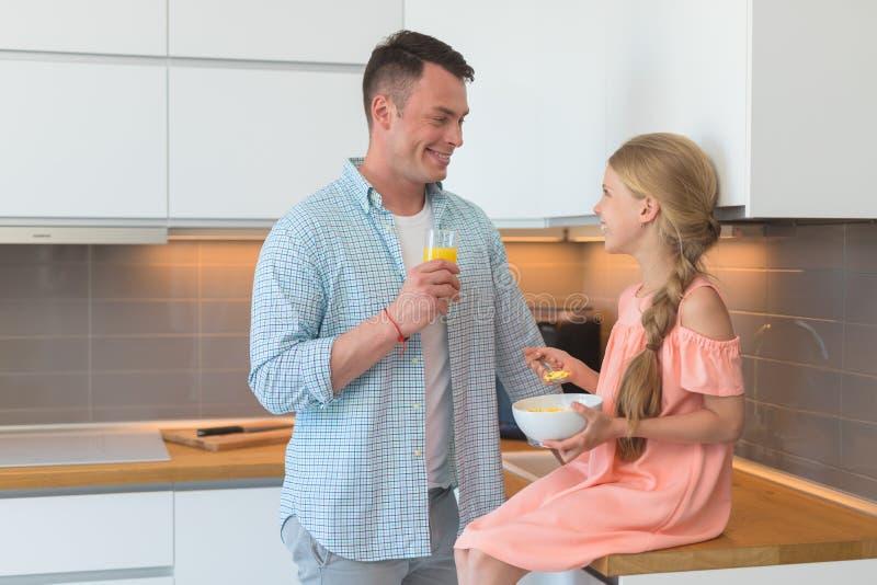 Ο νέος πατέρας και μια μικρή κόρη έχουν ένα πρόγευμα στοκ φωτογραφία με δικαίωμα ελεύθερης χρήσης
