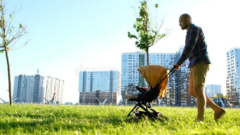 Ο νέος πατέρας κυλά ένα παιδί στο καροτσάκι μωρών στο πάρκο Άτομο που περπατά με το μωρό στη φύση στο ηλιοβασίλεμα, μετακίνηση κα στοκ φωτογραφίες