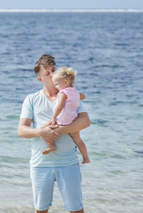 Ο νέος πατέρας φιλά τη μικρή κόρη του στην παραλία στοκ φωτογραφίες με δικαίωμα ελεύθερης χρήσης