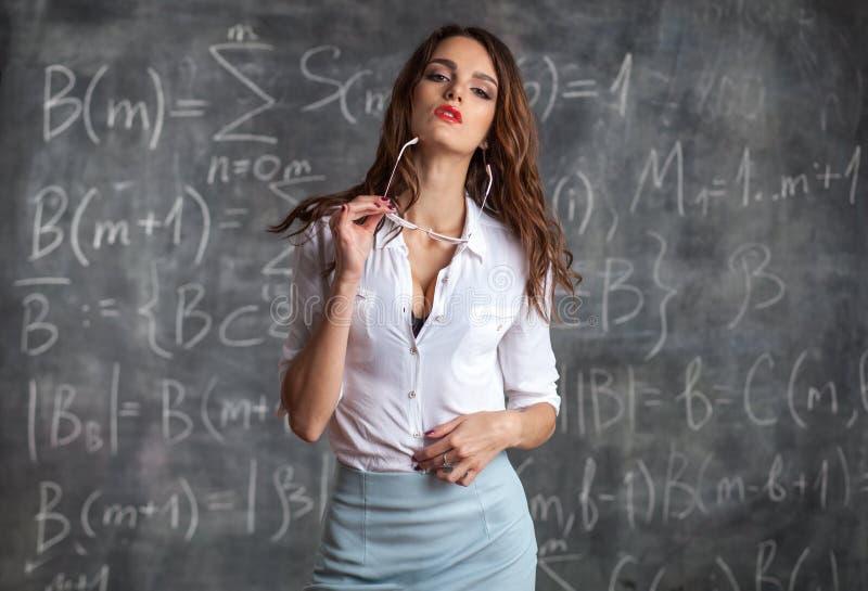 Ο νέος προκλητικός θηλυκός δάσκαλος κοντά στον πίνακα σε σεξουαλικό θέτει στοκ εικόνα