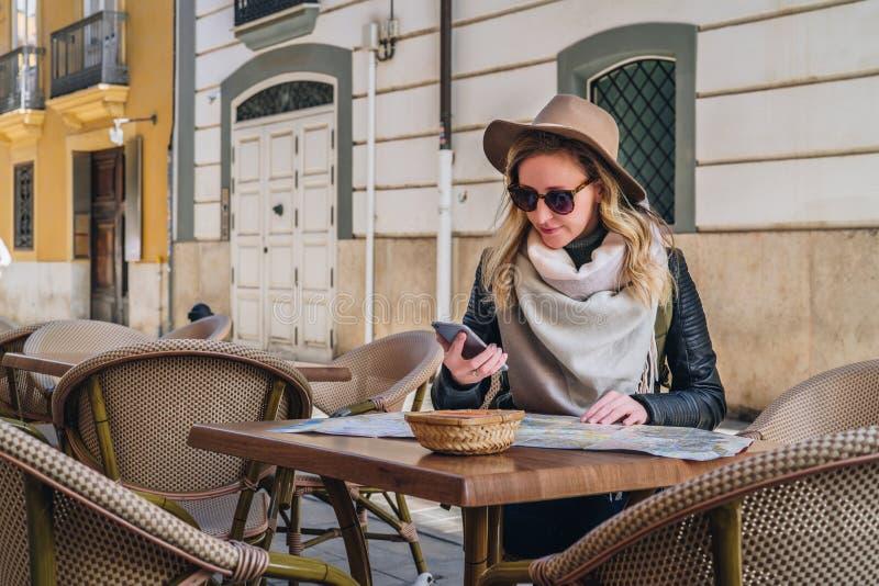Ο νέος τουρίστας γυναικών στα γυαλιά ηλίου και το καπέλο κάθεται στον καφέ οδών στον πίνακα, ψάχνοντας έναν τρόπο στο χάρτη, χρησ στοκ φωτογραφίες