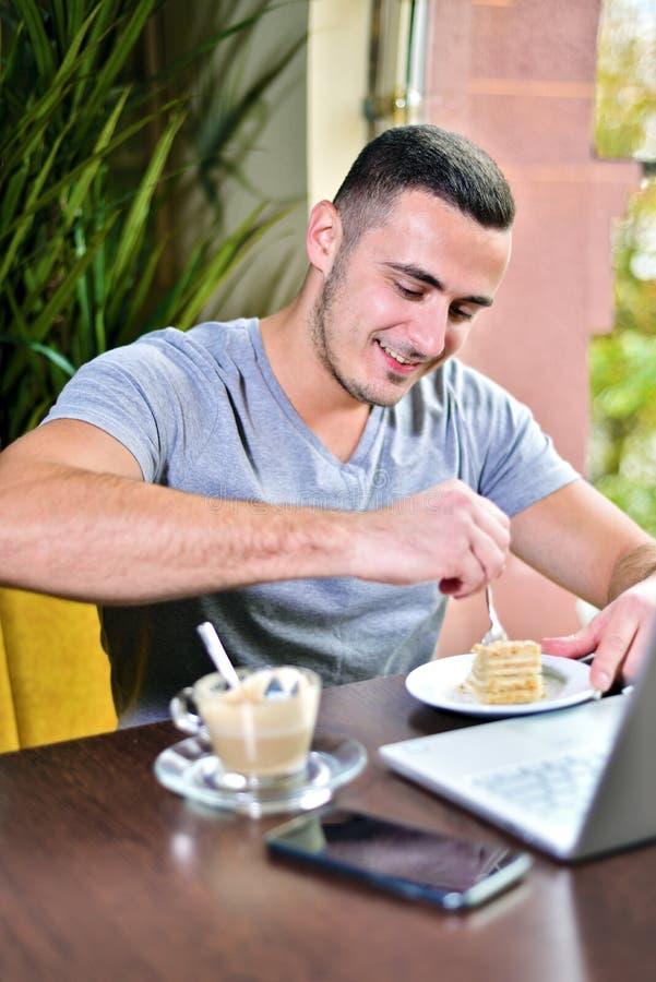 Ο νέος τύπος είναι freelancer στον καφέ που λειτουργεί πίσω από ένα lap-top πίνοντας άτομο καφέ στοκ φωτογραφίες με δικαίωμα ελεύθερης χρήσης