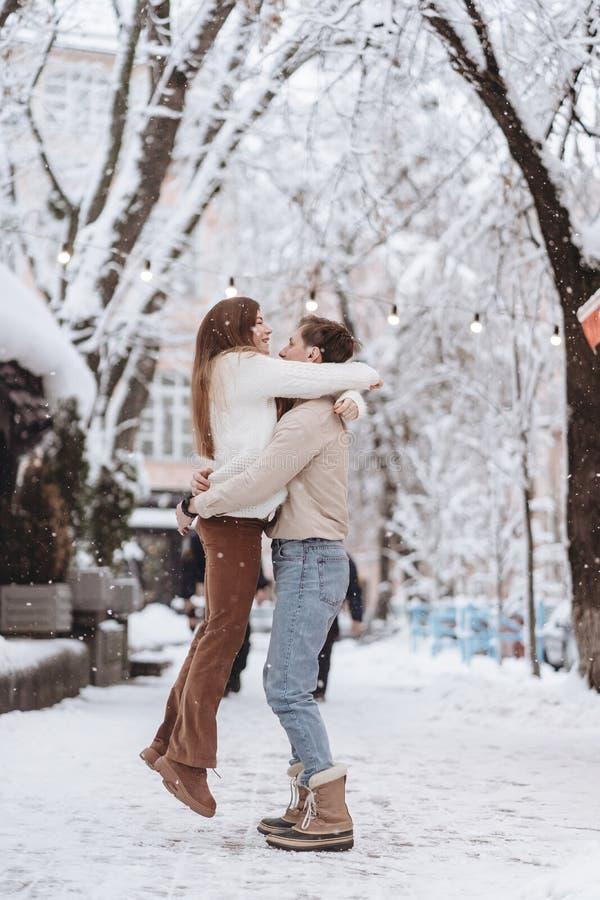 Ο νέος τύπος κρατά ένα όμορφο κορίτσι στα όπλα του Ζεύγος στα πουλόβερ στοκ φωτογραφίες