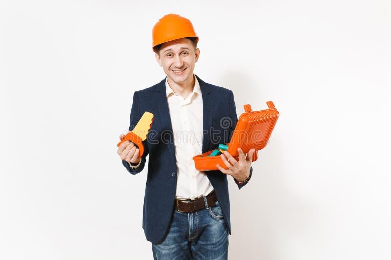 Ο νέος χαμογελώντας επιχειρηματίας στο σκοτεινό κοστούμι, προστατευτική εκμετάλλευση κρανών κατασκευής πορτοκαλιά άνοιξε την περί στοκ εικόνα