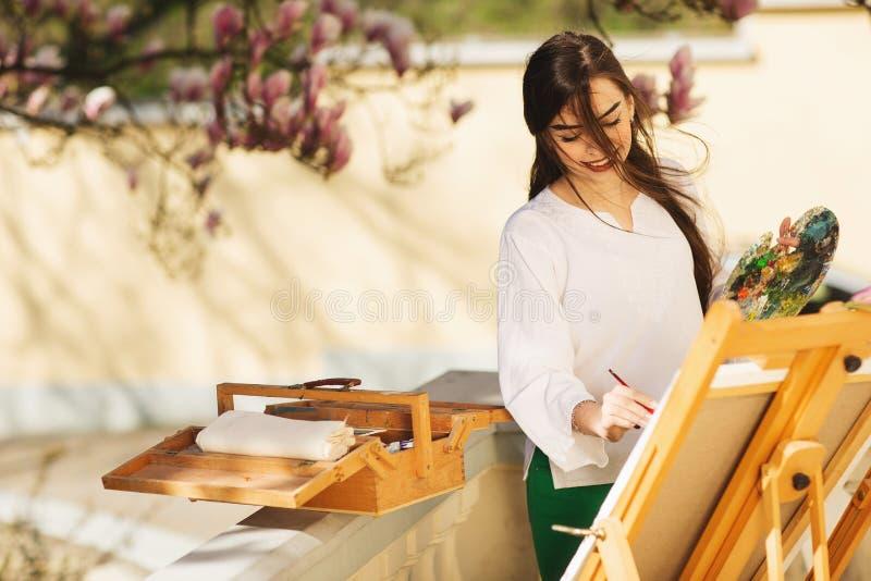 Ο νέος χαμογελώντας καλλιτέχνης γυναικών brunette χρωματίζει μια εικόνα στην οδό, κοντά σε ένα όμορφο δέντρο του magnolia στοκ εικόνες