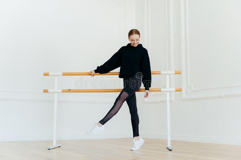 Ο νέος χορευτής μπαλέτου έχει την προθέρμανση, στέκεται κοντά στα κιγκλιδώματα, που ντύνονται στα μαύρα sportclothes, στάσεις στο στοκ εικόνες