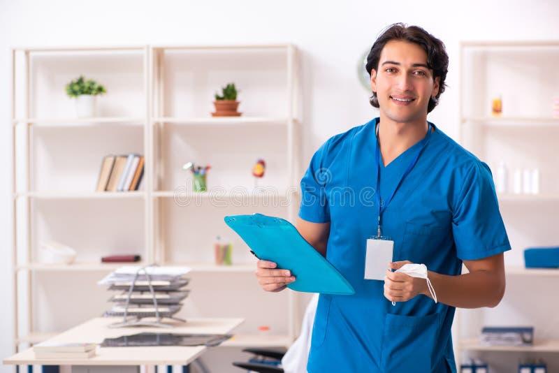Ο νέος όμορφος γιατρός που εργάζεται στην κλινική στοκ φωτογραφία με δικαίωμα ελεύθερης χρήσης