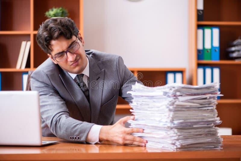 Ο νέος όμορφος επιχειρηματίας δυστυχισμένος με την υπερβολική εργασία στοκ φωτογραφία