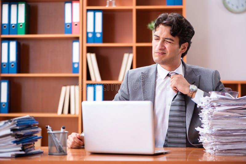 Ο νέος όμορφος επιχειρηματίας δυστυχισμένος με την υπερβολική εργασία στοκ εικόνες
