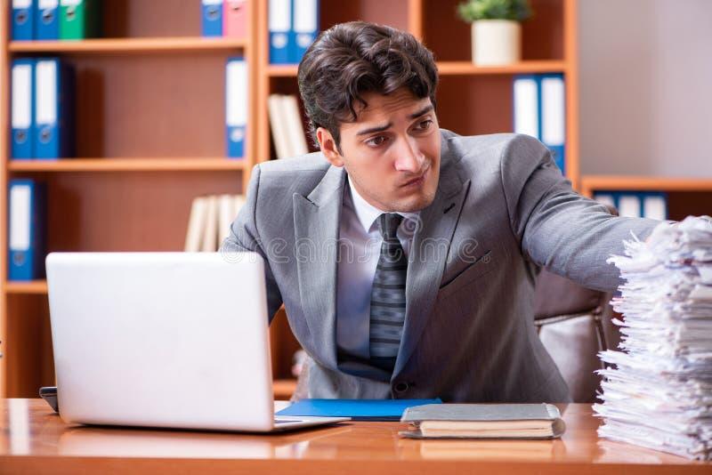 Ο νέος όμορφος επιχειρηματίας δυστυχισμένος με την υπερβολική εργασία στοκ εικόνα με δικαίωμα ελεύθερης χρήσης