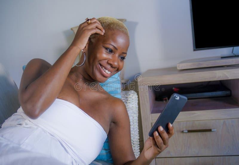 Ο νέος όμορφος και ευτυχής μαύρος καναπές γυναικών afro αμερικανικός στο σπίτι χαλάρωσε τα εύθυμα χρησιμοποιώντας Διαδίκτυο κοινω στοκ φωτογραφίες με δικαίωμα ελεύθερης χρήσης