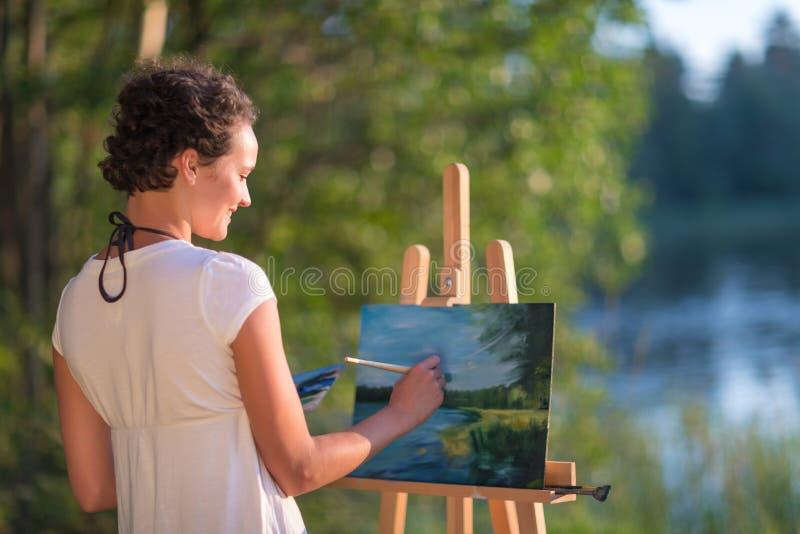 Ο νέος όμορφος καλλιτέχνης γυναικών επισύρει την προσοχή τα χρώματα μια εικόνα της λίμνης στη σαφή ύπαιθρο υπαίθρια στοκ φωτογραφία