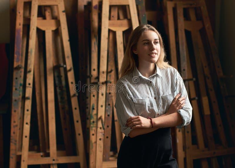 Ο νέος όμορφος σπουδαστής τέχνης ή αρχιτεκτονικής κοριτσιών ονειρεύεται το μέλλον της στο παλαιό ξύλινο easels υπόβαθρο στοκ εικόνα