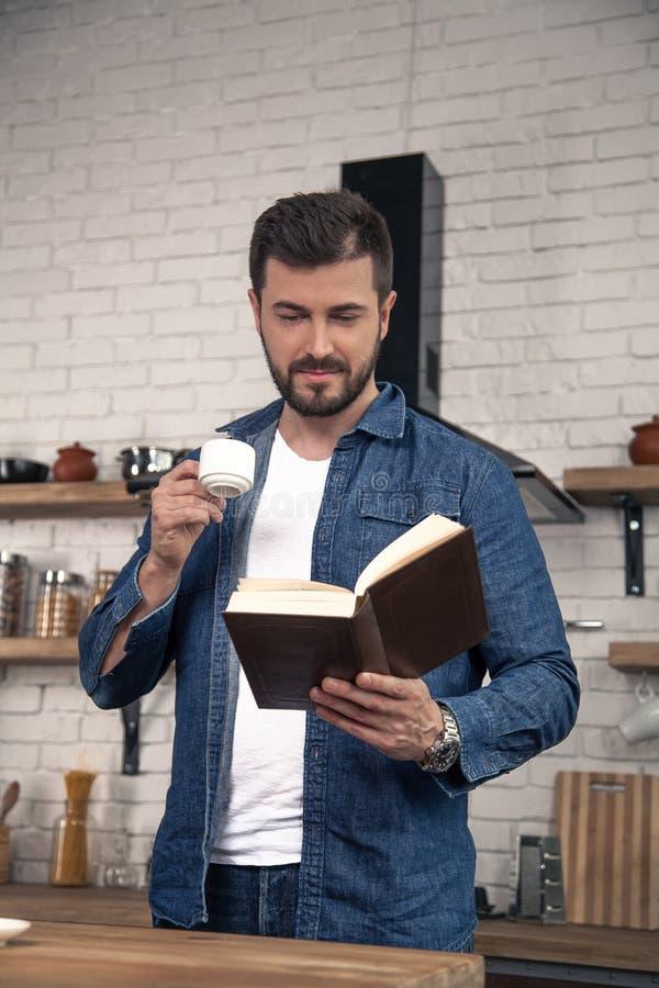 Ο νέος όμορφος τύπος έχει τον καφέ πρωινού του στην κουζίνα και διαβάζει ένα βιβλίο στοκ φωτογραφίες