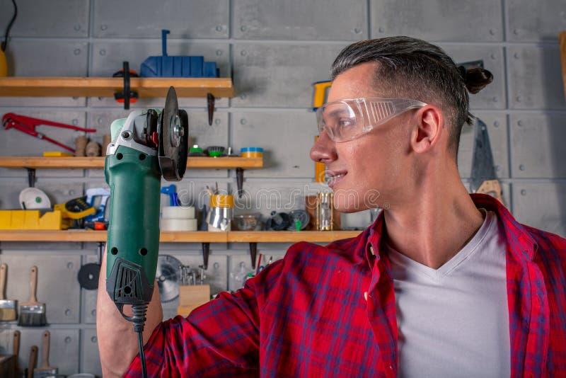 Ο νέος όμορφος χαμογελώντας καυκάσιος ξυλουργός που κρατά ένα κυκλικό πριόνι σε δικοί του παραδίδει το εργαστήριο έτοιμος να εργα στοκ εικόνες