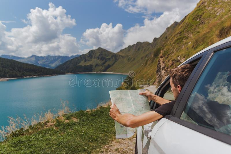 Ο νεαρός άνδρας έχασε στα βουνά με το αυτοκίνητό του ο χάρτης για να βρεί το σωστό δρόμο στοκ φωτογραφία