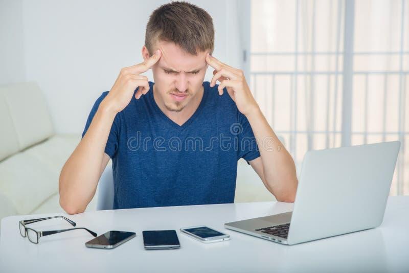 Ο νεαρός άνδρας έχει έναν πονοκέφαλο από τον υψηλό φόρτο εργασίας στοκ φωτογραφίες με δικαίωμα ελεύθερης χρήσης