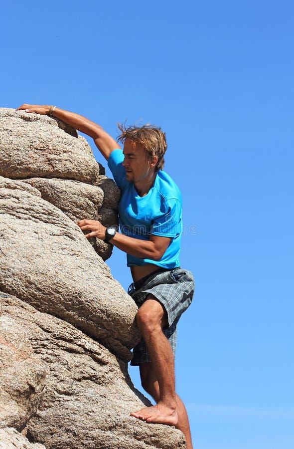Ο νεαρός άνδρας αναρριχείται σε έναν βράχο στοκ εικόνες