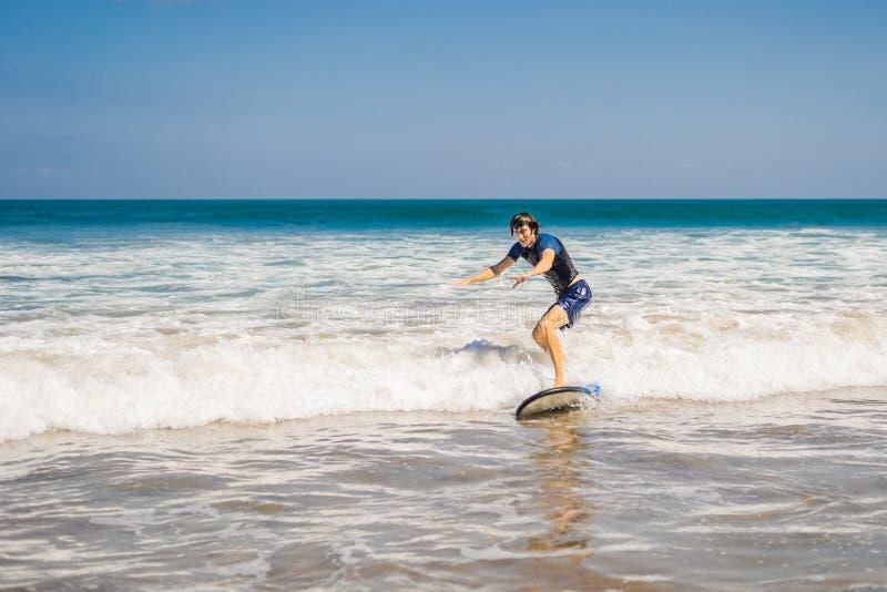 Ο νεαρός άνδρας, αρχάριος Surfer μαθαίνει να κάνει σερφ σε έναν αφρό θάλασσας στο Β στοκ φωτογραφία με δικαίωμα ελεύθερης χρήσης