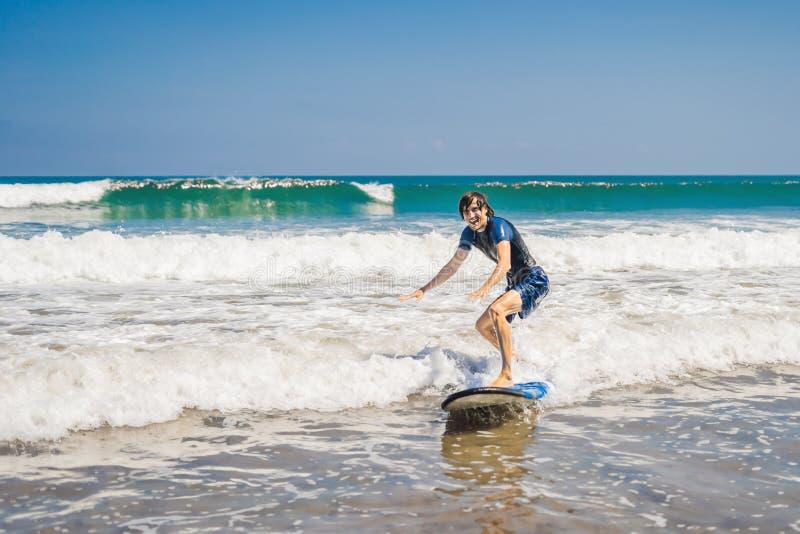 Ο νεαρός άνδρας, αρχάριος Surfer μαθαίνει να κάνει σερφ σε έναν αφρό θάλασσας στο Β στοκ εικόνες με δικαίωμα ελεύθερης χρήσης