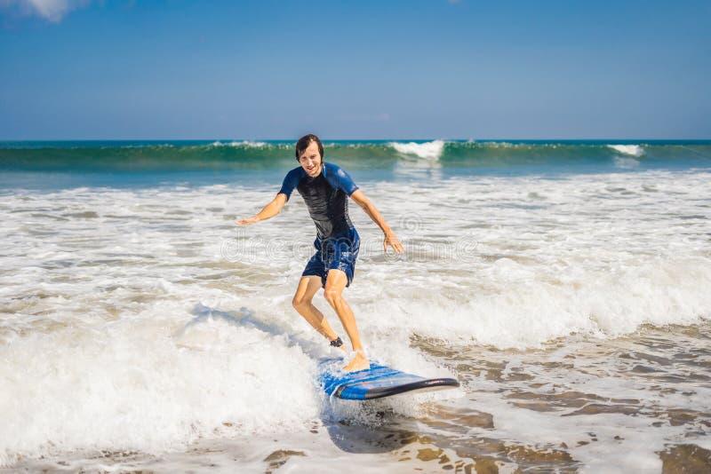 Ο νεαρός άνδρας, αρχάριος Surfer μαθαίνει να κάνει σερφ σε έναν αφρό θάλασσας στο Β στοκ εικόνες