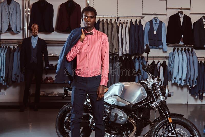 Ο νεαρός άνδρας αφροαμερικάνων έντυσε στην κομψή επίσημη τοποθέτηση ένδυσης κοντά στην αναδρομική αθλητική μοτοσικλέτα στο κατάστ στοκ φωτογραφία