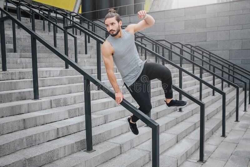 Ο νεαρός άνδρας είναι στην κίνηση Κρατά ένα χέρι στο εμπόδιο και πηδά πέρα από το Φαίνεται ευθύς Άλματα νεαρών άνδρων στα σκαλοπά στοκ φωτογραφία