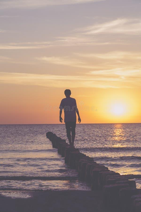 Ο νεαρός άνδρας ισορροπεί σε έναν βουβώνα στοκ εικόνες