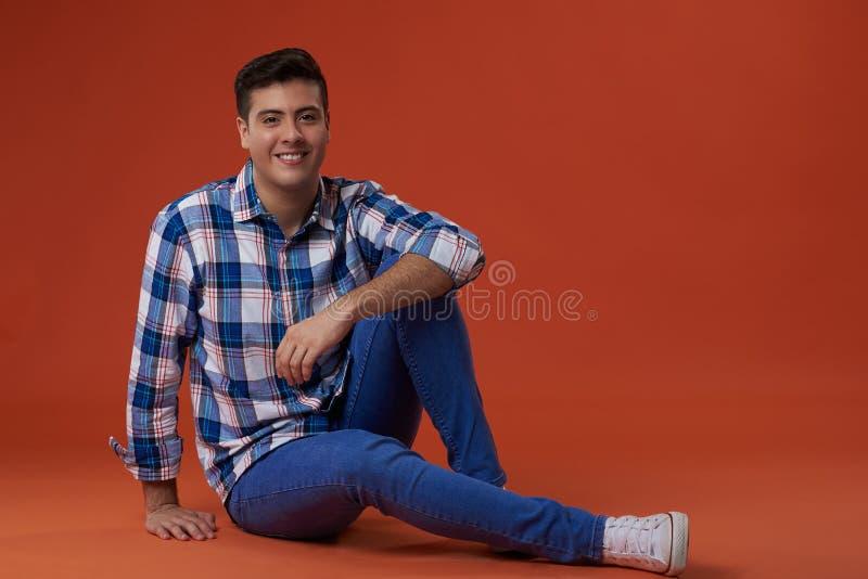 Ο νεαρός άνδρας κάθεται στο πάτωμα στοκ φωτογραφία με δικαίωμα ελεύθερης χρήσης