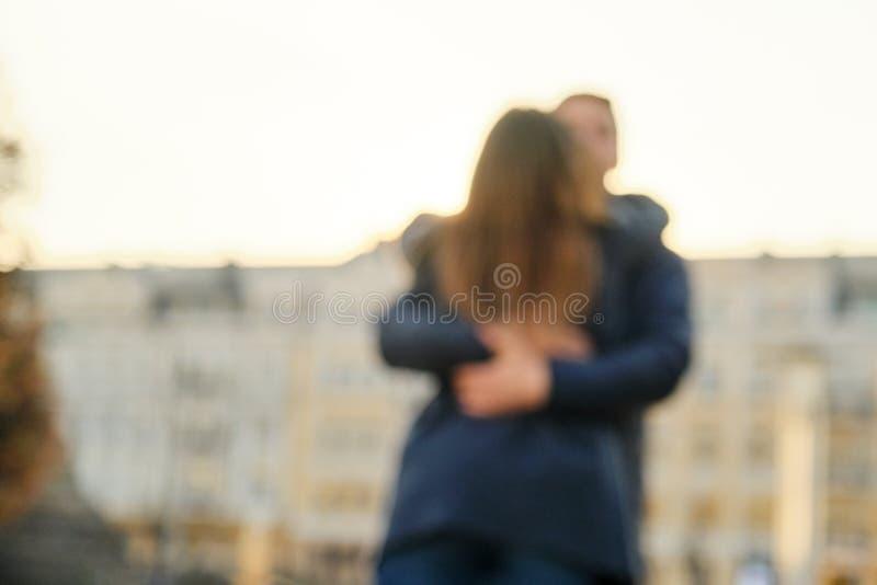 Ο νεαρός άνδρας και η γυναίκα που αγκαλιάζουν το φίλημα, ζεύγος θόλωσαν και μαλακή εστίαση, πόλη υποβάθρου, χρυσή ώρα στοκ εικόνες με δικαίωμα ελεύθερης χρήσης