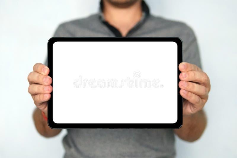 Ο νεαρός άνδρας κρατά μια ταμπλέτα μαξιλαριών αφής στο απομονωμένο άσπρο υπόβαθρο Η μεγάλου μεγέθους ψηφιακή ταμπλέτα με την άσπρ στοκ εικόνα
