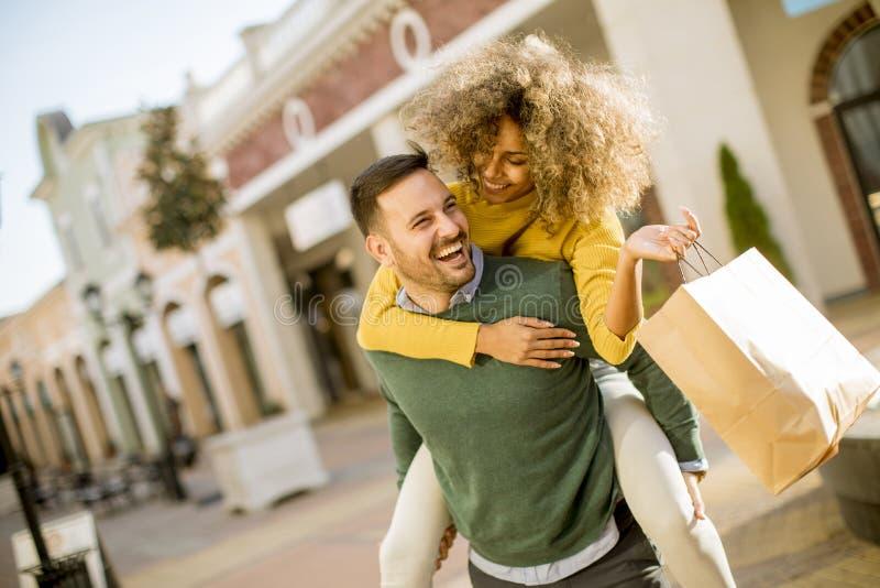 Ο νεαρός άνδρας κρατά τη νέα γυναίκα στην πλάτη του, έχει τη διασκέδαση και πηγαίνει στο sho στοκ εικόνες με δικαίωμα ελεύθερης χρήσης
